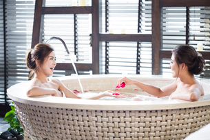 Beautiful young women in bathtub with rose petalsの写真素材 [FYI02637114]