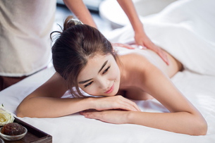 Young woman receiving back massage at spa centerの写真素材 [FYI02637115]