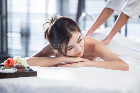 Young woman receiving back massage at spa centerの写真素材 [FYI02637121]