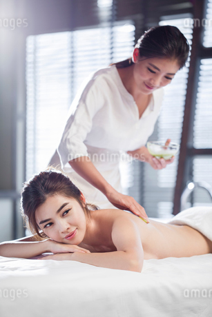 Young woman receiving back massage at spa centerの写真素材 [FYI02637133]