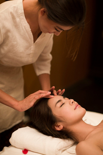 Young woman receiving facial massage at spa centerの写真素材 [FYI02637138]