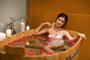 Beautiful young woman in bathtub with rose petalsの写真素材 [FYI02637150]