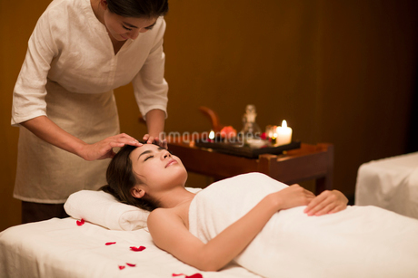 Young woman receiving facial massage at spa centerの写真素材 [FYI02637156]