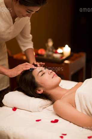 Young woman receiving facial massage at spa centerの写真素材 [FYI02637159]
