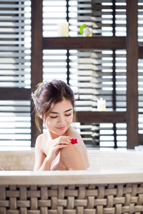 Beautiful young woman in bathtub with rose petalsの写真素材 [FYI02637198]