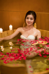 Beautiful young woman in bathtub with rose petalsの写真素材 [FYI02637237]