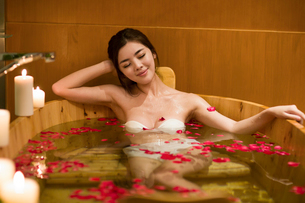 Beautiful young woman in bathtub with rose petalsの写真素材 [FYI02637247]