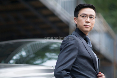 Mid adult businessman standing next to the carの写真素材 [FYI02637608]