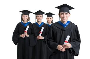 Happy college graduates in graduation gownsの写真素材 [FYI02638454]