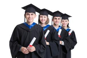 Happy college graduates in graduation gownsの写真素材 [FYI02638458]