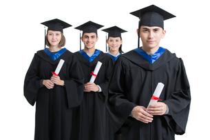Happy college graduates in graduation gownsの写真素材 [FYI02638463]