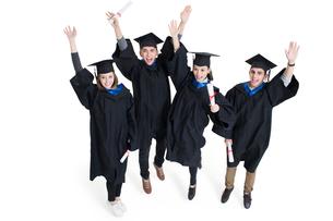 Happy college graduates in graduation gowns wavingの写真素材 [FYI02638466]