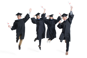 Happy college graduates in graduation gowns jumpingの写真素材 [FYI02638467]
