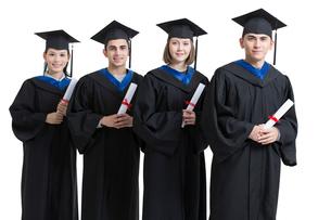 Happy college graduates in graduation gownsの写真素材 [FYI02638468]