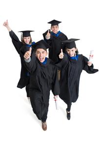 Happy college graduates in graduation gowns doing thumbs upの写真素材 [FYI02638472]