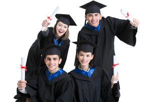 Happy college graduates in graduation gownsの写真素材 [FYI02638473]