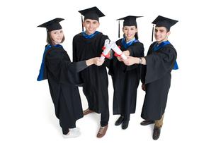 Happy college graduates in graduation gownsの写真素材 [FYI02638474]