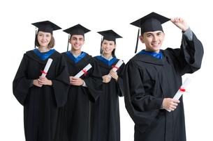 Happy college graduates in graduation gownsの写真素材 [FYI02638475]