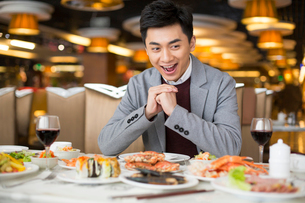 Cheerful young Chinese man having buffet dinnerの写真素材 [FYI02638513]