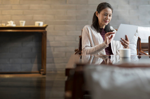 Elegance mature Chinese woman using digital tablet in cafeの写真素材 [FYI02638803]