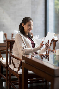 Elegance mature Chinese woman using digital tablet in cafeの写真素材 [FYI02638813]