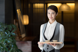 Elegance Chinese waitress holding two cups of teaの写真素材 [FYI02638917]