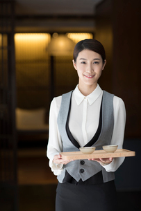 Elegance Chinese waitress holding two cups of teaの写真素材 [FYI02638927]