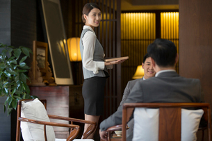 Elegance Chinese waitress holding a trayの写真素材 [FYI02639030]