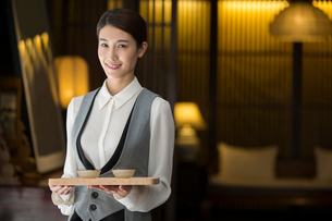 Elegance Chinese waitress holding two cups of teaの写真素材 [FYI02639031]