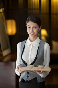 Elegance Chinese waitress holding two cups of teaの写真素材 [FYI02639035]