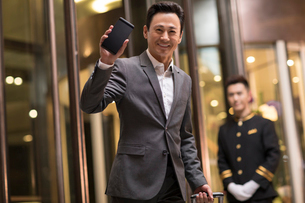 Cheerful Chinese businessman holding a smart phoneの写真素材 [FYI02639238]