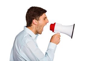 Young man shouting through megaphoneの写真素材 [FYI02639480]