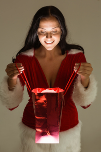 Smiling woman opening christmas presentの写真素材 [FYI02639510]