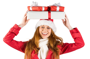 Festive redhead holding pile of giftsの写真素材 [FYI02639519]