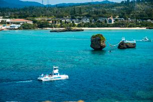 沖縄万座毛断崖から万座ビーチ方面エメラルドグリーンの海とトベラ岩に観光船の写真素材 [FYI02641618]