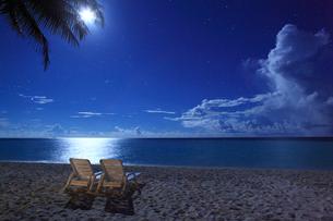 月明かりに照らされたビーチとペアのイスの写真素材 [FYI02643772]