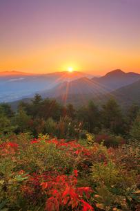 浅間山から昇る朝日と冠着山などの山並みと紅葉の樹林の写真素材 [FYI02644777]