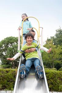 公園の滑り台の子供男女3人の写真素材 [FYI02645023]