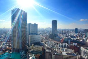 タワー型マンションと新宿方向のビル群と太陽の光芒の写真素材 [FYI02645492]