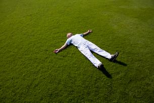公園の芝生で大の字に寝る中高年男性の写真素材 [FYI02645577]