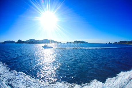 安慶名敷島と嘉比島など慶良間諸島と船と太陽の光芒の写真素材 [FYI02645583]