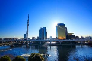 東京スカイツリーとアサヒビールタワーと隅田川と船と朝の漏れ日の写真素材 [FYI02645713]