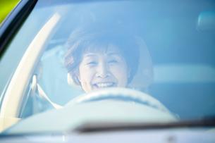 運転席に座る笑顔のシニア女性の写真素材 [FYI02645748]
