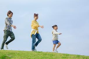 丘を歩く笑顔の家族の写真素材 [FYI02645752]