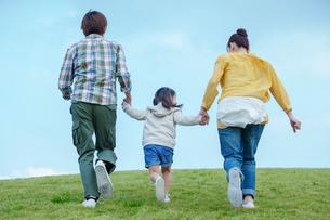 手をつなぎ走る家族の後ろ姿の写真素材 [FYI02645903]