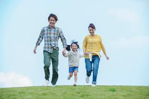手をつなぎ走る笑顔の日本人家族の写真素材 [FYI02645967]