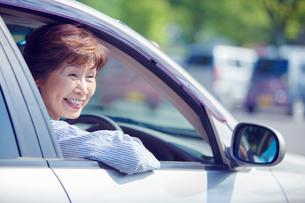 運転席に座る笑顔のシニア女性の写真素材 [FYI02646001]