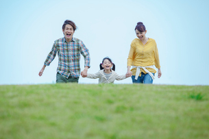 手をつなぎ歩く笑顔の日本人親子の写真素材 [FYI02646005]