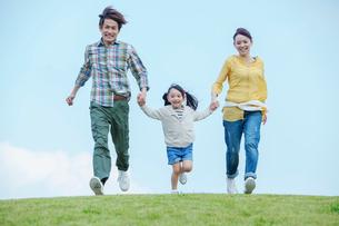 手をつなぎ走る笑顔の日本人親子の写真素材 [FYI02646059]