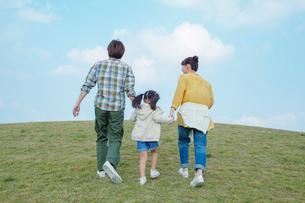 手をつなぎ歩く親子の後ろ姿の写真素材 [FYI02646065]